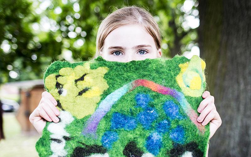 Ein Mädchen hält ihre Filzlandschaft ins Bild