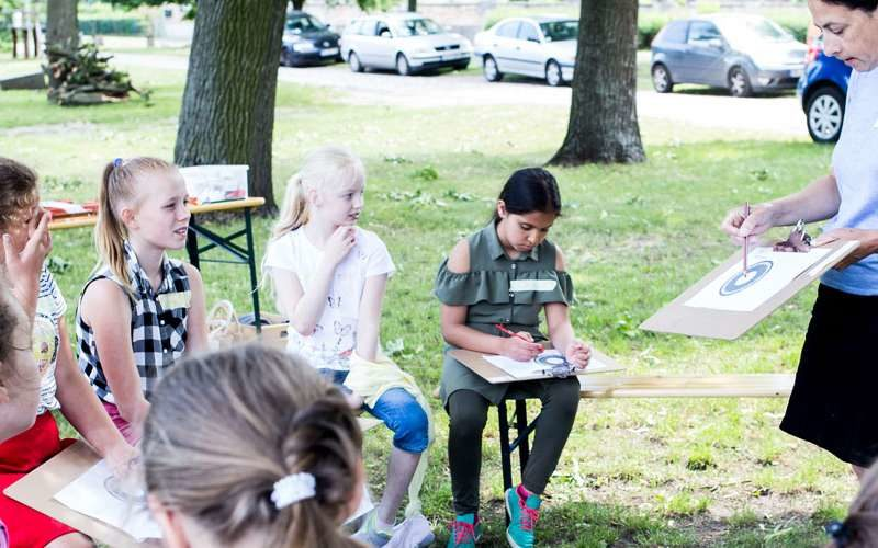 Gruppe Mädchen beim Unterricht im Grünen