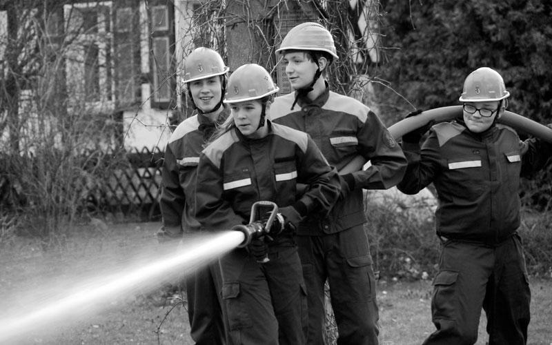 junge Feuerwehrmänner mit Spritzenschlauch